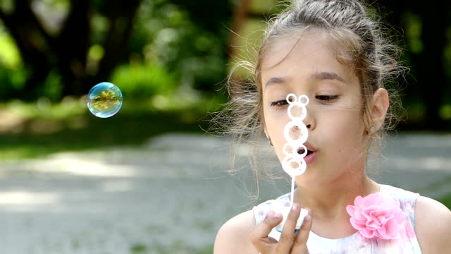 Little girl blowing soap bubbles in park-slowmotion video