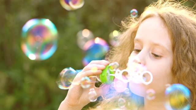 Little girl blowing soap bubbles in summer park. video