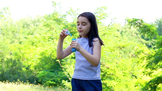 Little Girl blowing soap bubbles video