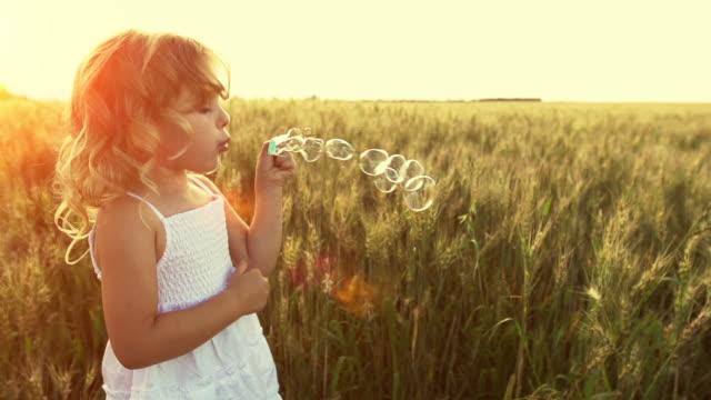 Little girl blows bubbles