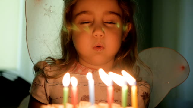 Little girl blows out candles on birthday cake at party. Closeup. Slow motion. Little girl blows out candles on birthday cake at party. Closeup. Slow motion. happy birthday stock videos & royalty-free footage