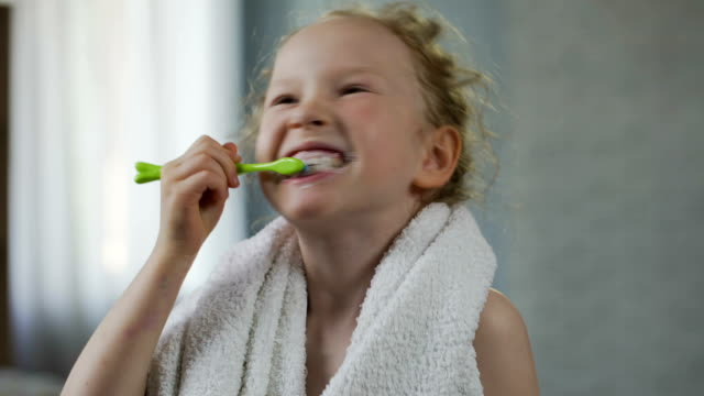 Little girl brushing her teeth diligently, dental hygiene, morning ritual video