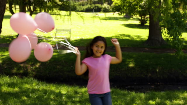 little girl carrying balloons for breast cancer awareness - breast cancer awareness 個影片檔及 b 捲影像