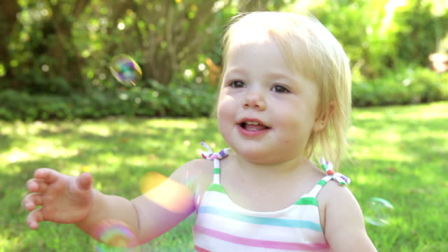 Little Girl Catching Bubbles In Garden video
