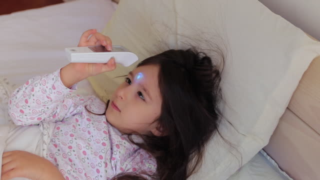 Little girl checking her own body temperature with infrared thermometer Little girl lying in bed and checking her own body temperature with infrared thermometer at home double bed stock videos & royalty-free footage