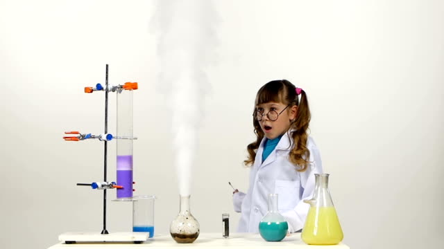 Little girl chemist with two ponytails in uniform, protective glasses has successfully tested the new formula and wonders, on white background, slow motion video