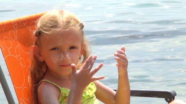 little girl, child applying sunscreen lotion on beach, coastline - sun cream stock videos & royalty-free footage
