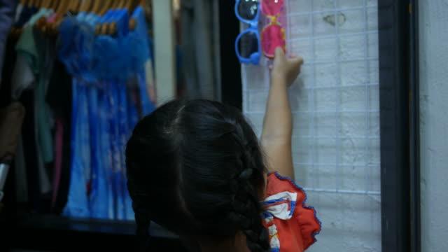 little girl choosing dress in boutique shop video