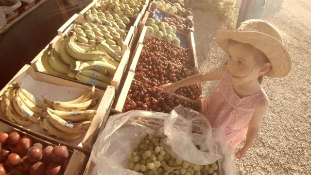little girl choosing fruit at farmers market - pesche bambino video stock e b–roll