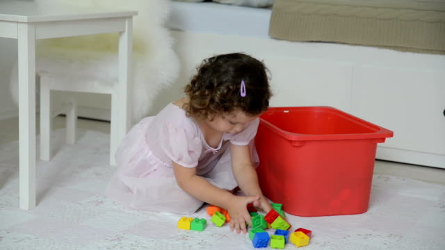 Little girl cleaning up colorful kids toys video