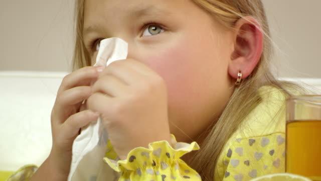 vídeos y material grabado en eventos de stock de little girl tos y limpiar su nariz. - flu
