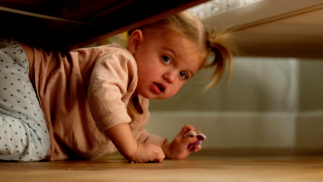 Little girl crawling under bed