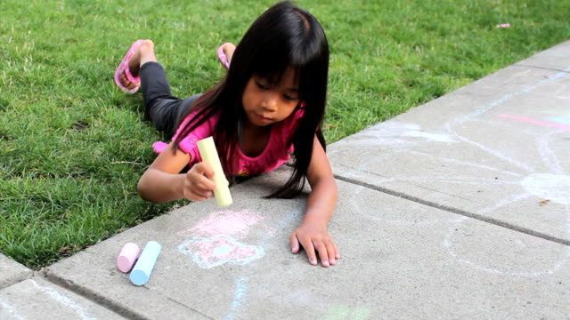 Little Girl Creating Sidewalk Art Using Chalk A cute little Asian girl enjoys creating some pretty sidewalk chalk art on a lovely summer day. Need more clips of kids? thai ethnicity stock videos & royalty-free footage