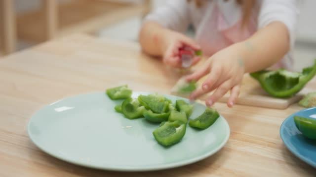 vídeos y material grabado en eventos de stock de niña pequeña cortando un pimiento verde - pimiento verde