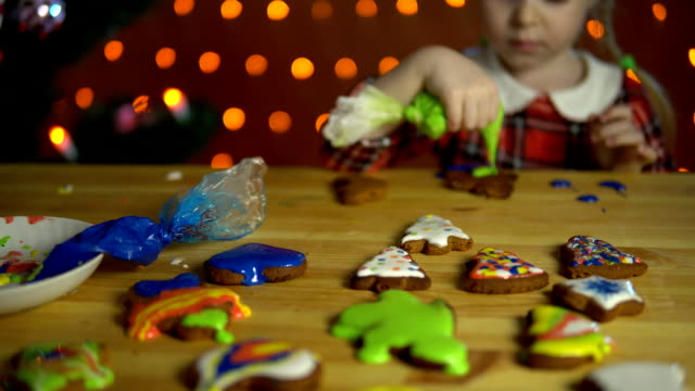 A little girl decorates gingerbread next to a Christmas tree in the evening. video