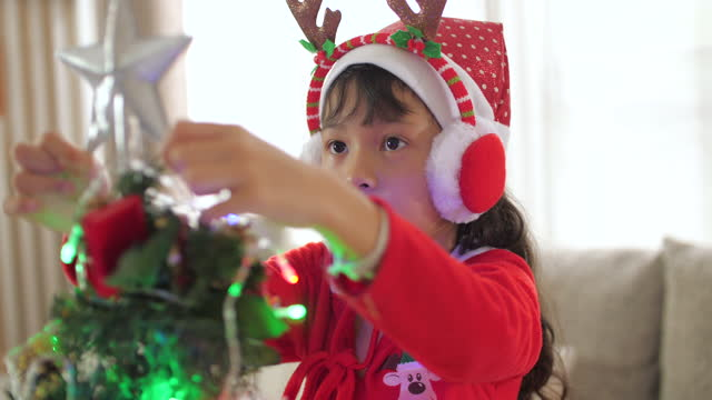 Little girl Decorating the Christmas tree by Ornaments in Christmas time