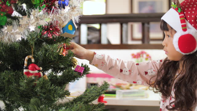 Little girl Decorating the Christmas tree by Ornaments in Christmas time Asian girl Decorating the Christmas tree , 4K(UHD) , slow motion , Christmas concept christmas stocking stock videos & royalty-free footage