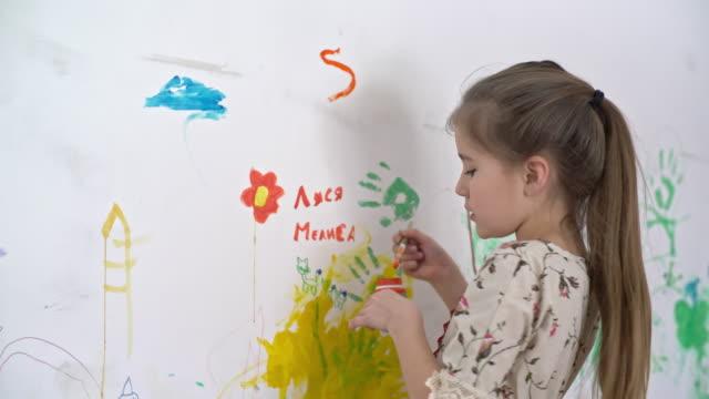 그녀의 방에 있는 작은 소녀 장식 벽 - kids drawing 스톡 비디오 및 b-롤 화면