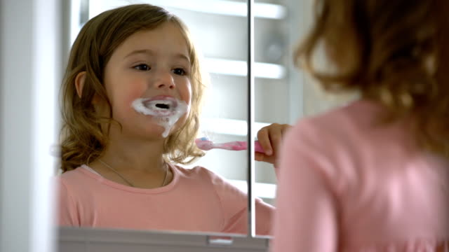 Little girl diligently brushing his teeth in the mirror. video