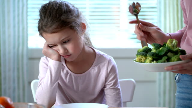 little girl do not want to eat vegetables and dislike taste of broccoli and spinach. - furioso video stock e b–roll