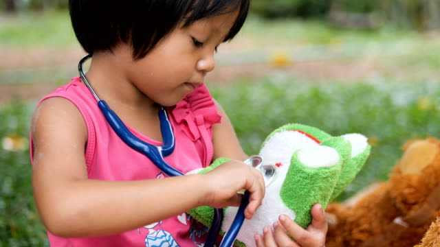 Little girl doctor saving her frog doll friend
