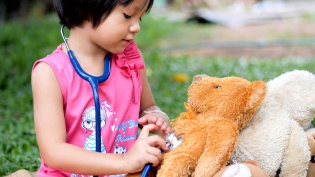 Little girl doctor saving her teddy bear friend