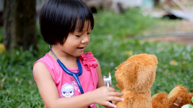 Little girl doctor saving her teddy bear friend Little girl doctor saving her teddy bear friend dressing up stock videos & royalty-free footage