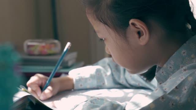 liten flicka gör sin hemläxa - working from home bildbanksvideor och videomaterial från bakom kulisserna