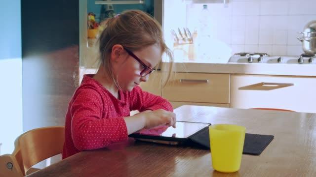 bambina che disegna su tavoletta a casa. bambino che disegna su tablet dispositivo in cucina sull'istruzione a distanza. ragazza che fa i compiti su tablet. educazione intelligente. scuola a casa. insegnamento a distanza - didattica a distanza video stock e b–roll