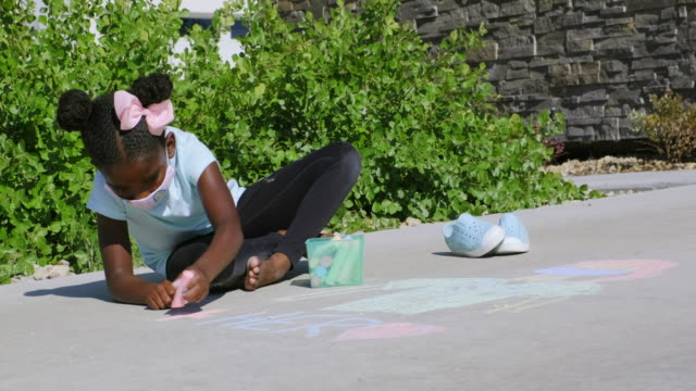 Little Girl Drawing with Sidewalk Chalk to Support Healthcare Workers