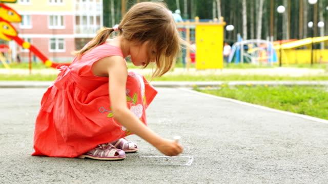 kleines mädchen zeichnen mit kreide auf asphalt im freien - kreide weiss stock-videos und b-roll-filmmaterial