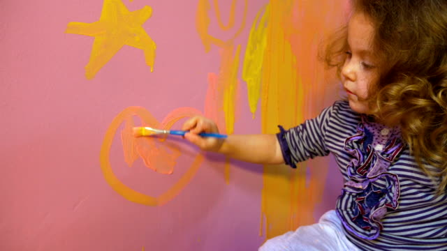 Little girl draws on wall stars and heart