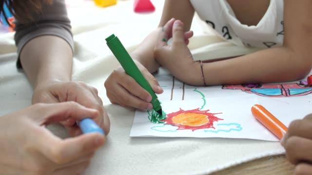 la bambina disegna con la madre - arti e mestieri video stock e b–roll