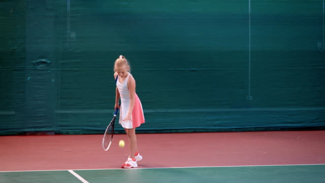 Little girl dressed in sport outfit is having training at indoor tennis court. Young female sportswoman is playing professional tennis and bouncing yellow ball before hitting it with racket video