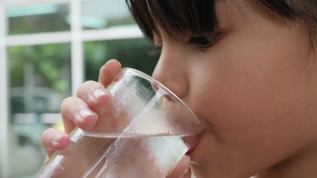 stockvideo's en b-roll-footage met weinig meisje drinken vers water na spelen - water drinken