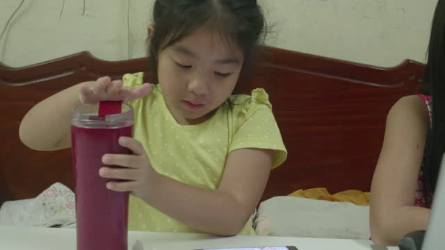 Little girl drinking water during attending to online class from home