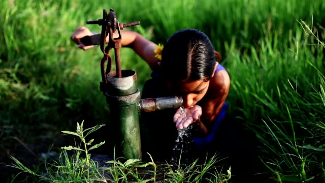 Little girl drinking water near green field Elevated view of little girl of Indian ethnicity drinking water near green field outdoor in the nature. poverty stock videos & royalty-free footage