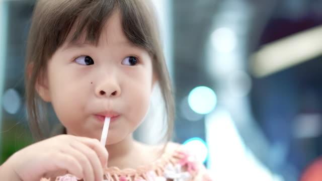 vídeos y material grabado en eventos de stock de poco niña agua potable a través de una paja - zumo