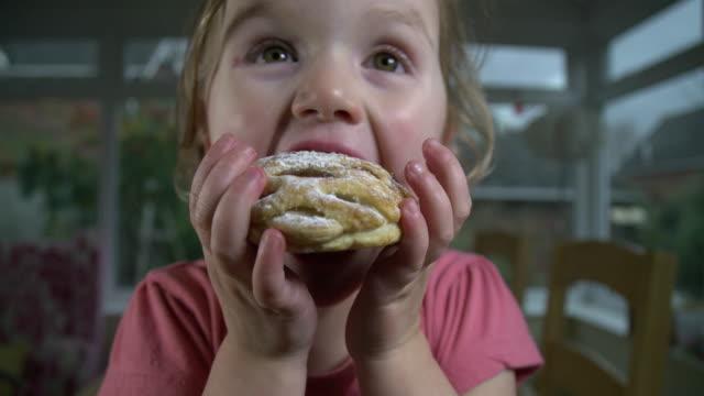 küçük kız bir ev yedeklenmiş börek yemek - pasta stok videoları ve detay görüntü çekimi