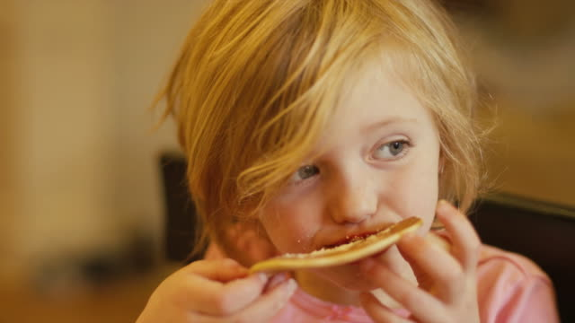 a little girl eating a pancake with her hands, close up, slow motion - pancake video stock e b–roll