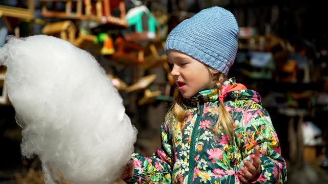 Little Girl Eating Cotton Candy in a Park Funny Little Girl Greedily Eating Cotton Candy in Spring Sunny Day in a Park cotton candy stock videos & royalty-free footage