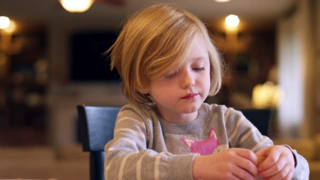 A little girl eating crackers at the kitchen counter, with bokeh behind her, slow motion video
