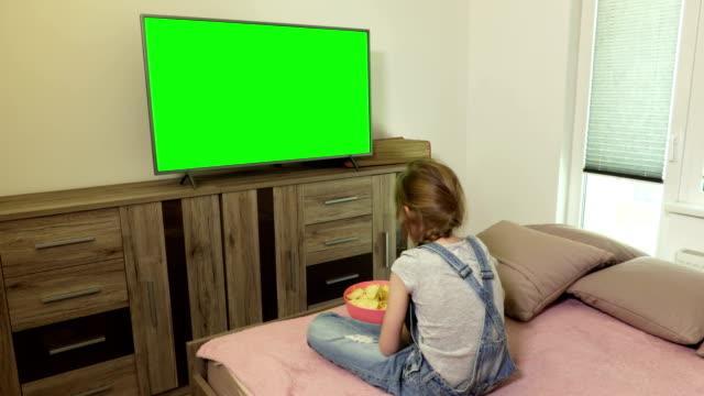 vídeos de stock e filmes b-roll de little girl eating crisps and watching tv with green screen - tv e familia e ecrã