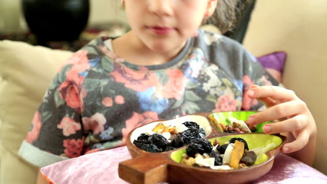 Little girl eating dried fruit video