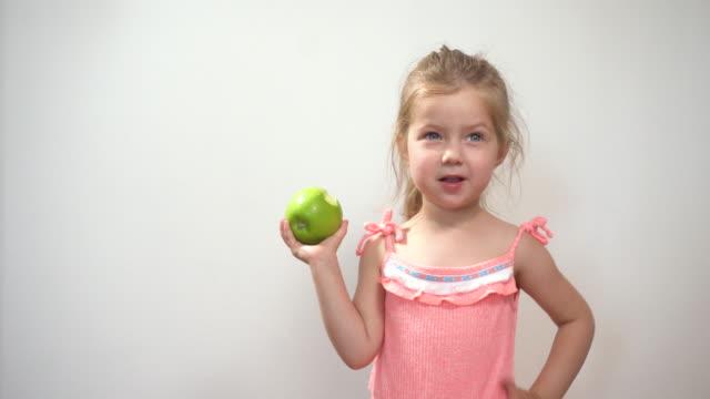 liten flicka äter grönt färskt surt äpple på vit bakgrund - endast flickor bildbanksvideor och videomaterial från bakom kulisserna