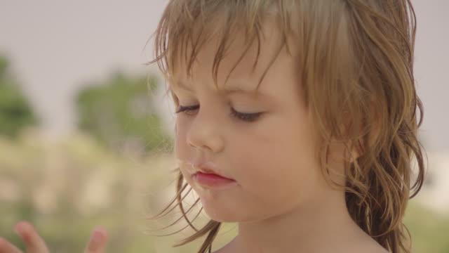 Little girl eating ice cream on the beach
