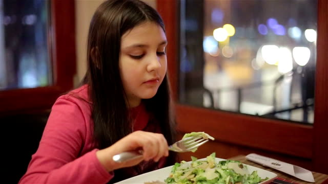 little girl eating in restaurant video