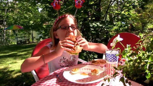 Little girl eats hamburger outside on a sunny day video
