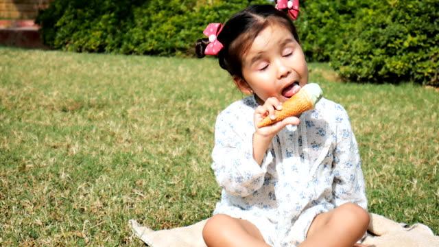 little girl eats ice cream. - nastro per capelli video stock e b–roll