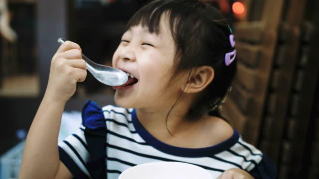 Little girl enjoy eating Happy little girl enjoy eating with ice cream, Bangkok Thailand spoon stock videos & royalty-free footage